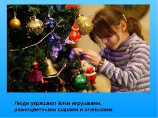 Люди украшают ёлки игрушками, разноцветными шарами и огоньками.