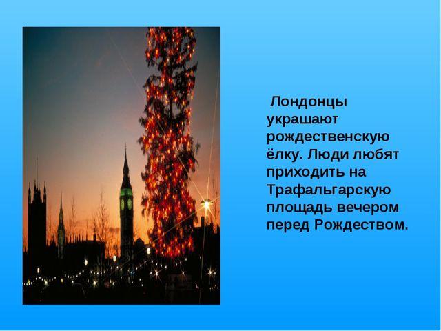 Лондонцы украшают рождественскую ёлку. Люди любят приходить на Трафальгарску...