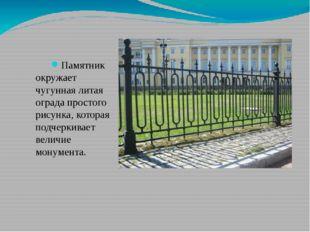 Памятник окружает чугунная литая ограда простого рисунка, которая подчеркива