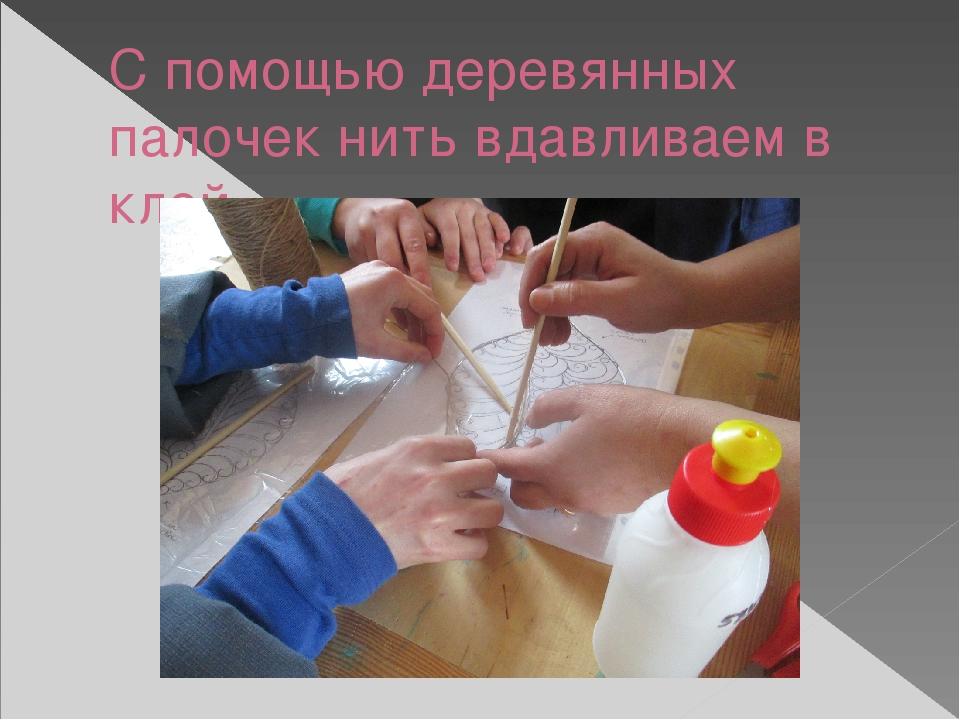 С помощью деревянных палочек нить вдавливаем в клей
