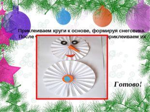 Приклеиваем круги к основе, формируя снеговика. После чего врезаем детали лиц