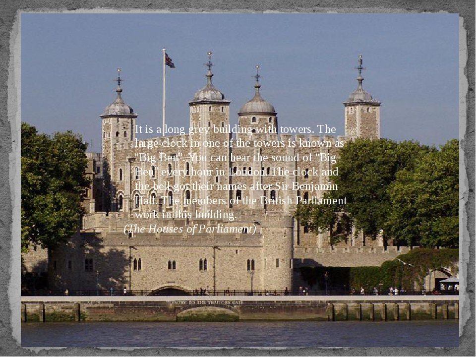 It is a long grey building with towers. The large clock in one of the towers...
