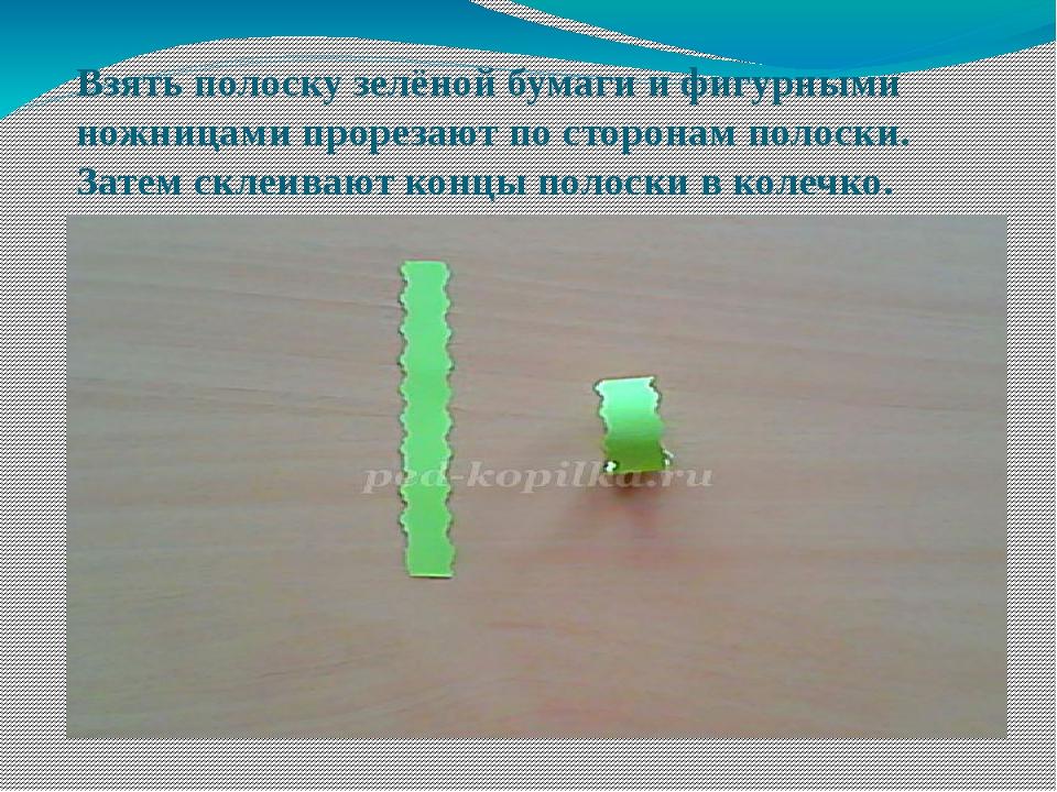 Взять полоску зелёной бумаги и фигурными ножницами прорезают по сторонам поло...
