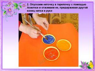 2. Опускаем ниточку в тарелочку с помощью ложечки и отжимаем ее, придерживая