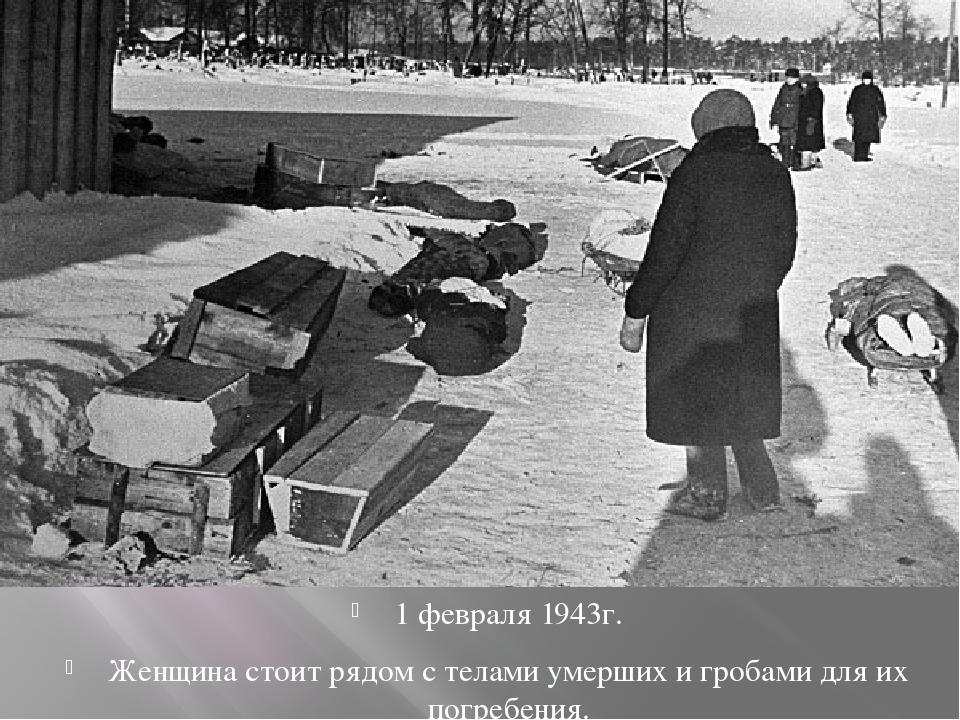 1 февраля 1943г. Женщина стоит рядом с телами умерших и гробами для их погре...