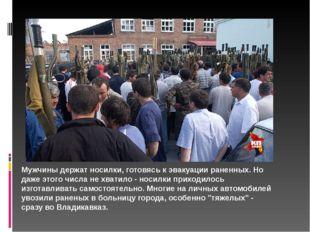 Мужчины держат носилки, готовясь к эвакуации раненных. Но даже этого числа не
