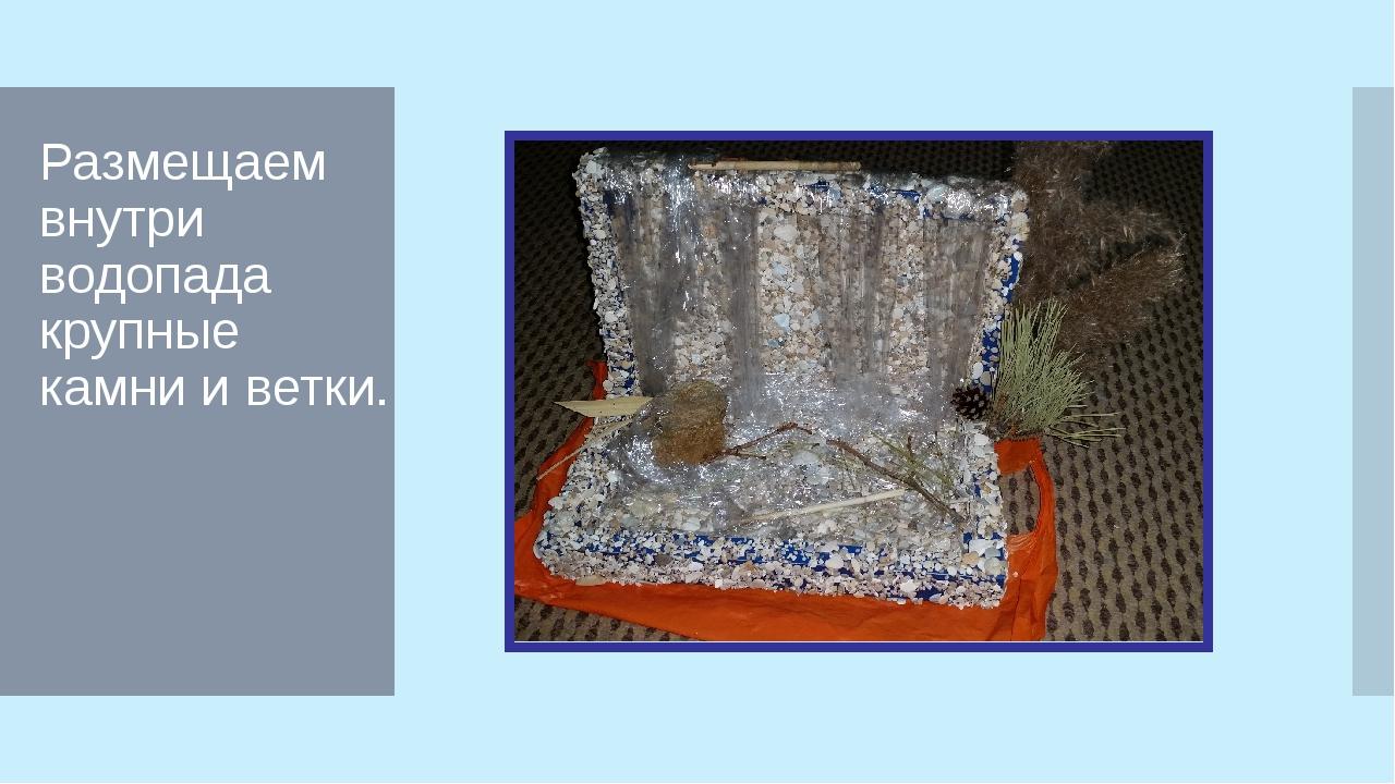 Размещаем внутри водопада крупные камни и ветки.