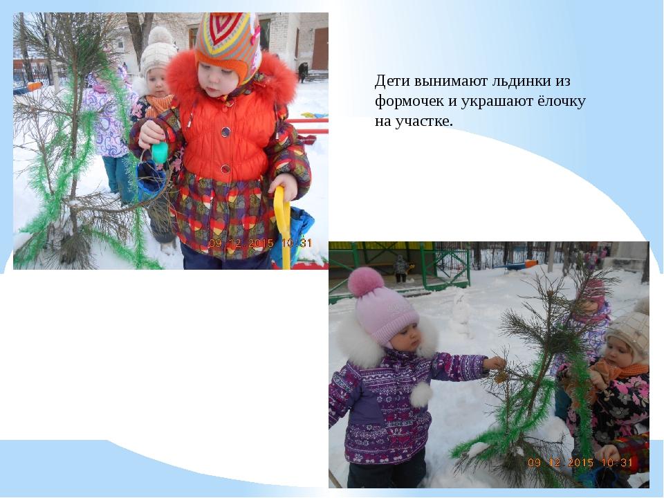 Дети вынимают льдинки из формочек и украшают ёлочку на участке.