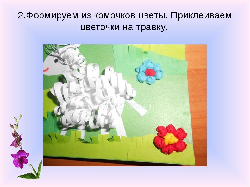 2.Формируем из комочков цветы. Приклеиваем цветочки на травку.