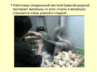 Работница специальной жесткой бумагой-шкуркой протирает матрёшку со всех стор