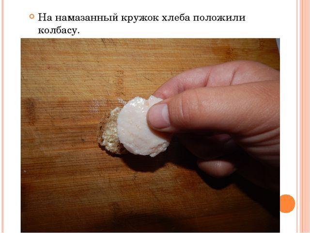 На намазанный кружок хлеба положили колбасу.