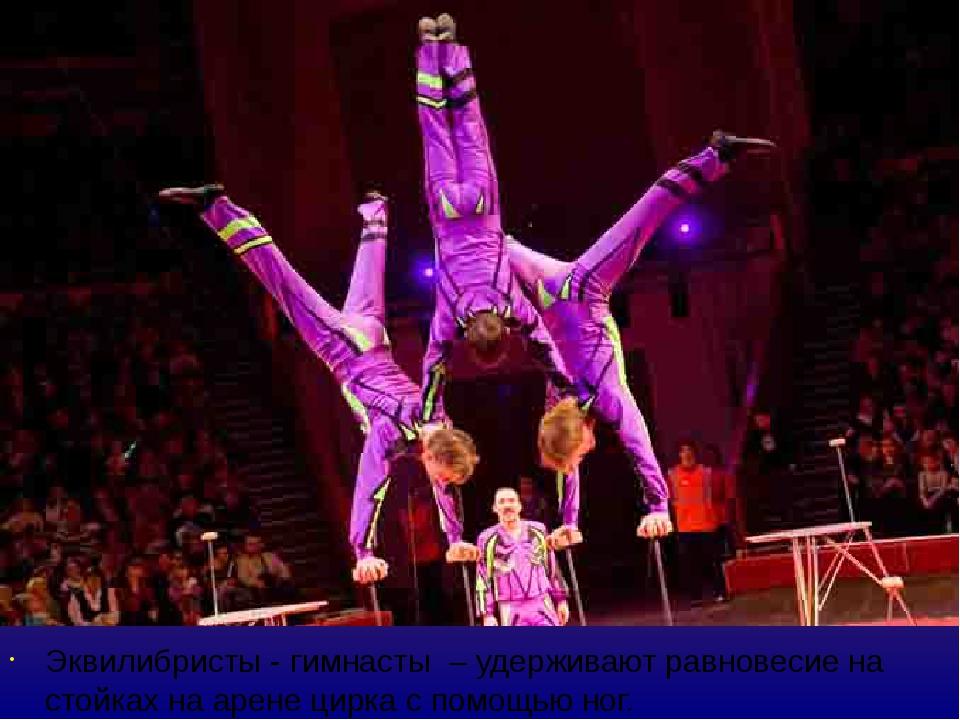 Эквилибристы - гимнасты – удерживают равновесие на стойках на арене цирка с п...
